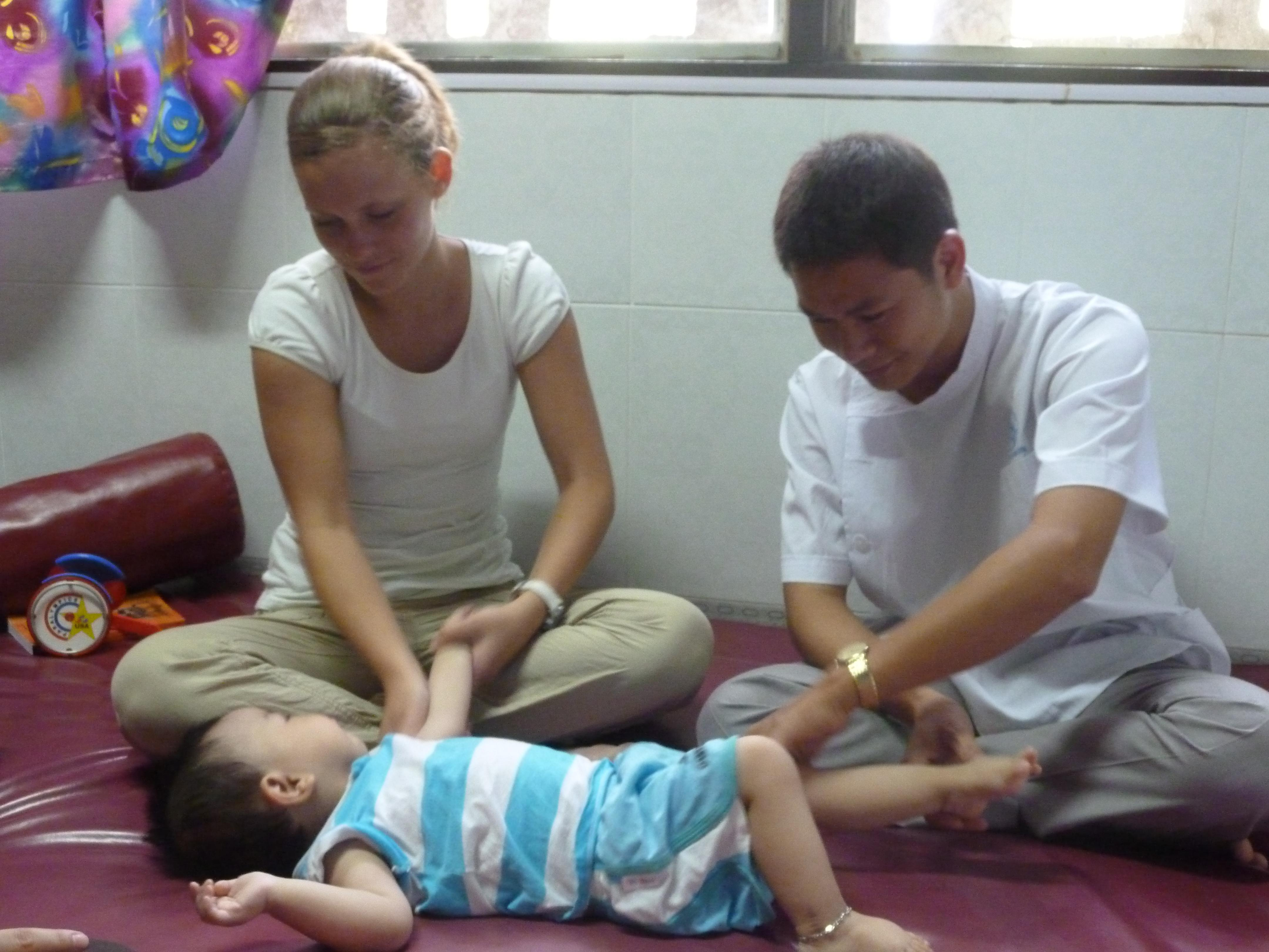 A female intern is pictured helping a local doctor encourage movement in a baby during her occupational therapy internship in Vietnam.